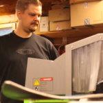 Harri Heikkinen käyttää uutta hiomakonetta, joka terottaa suksen kantit automaattisesti.