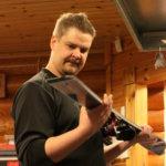 Harri Heikkinen huoltaa ja voitelee suksia alkavaa kautta varten.