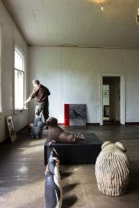 Näyttelyä järjestellään yhä. Jukka Tuominen ripustamassa taulujaan. Etualalla Teemu Luodon eläinteoksia.
