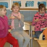Tuula Lehto näyttöää, miten kankakerä laiteetaan. oppilaat katselevat.