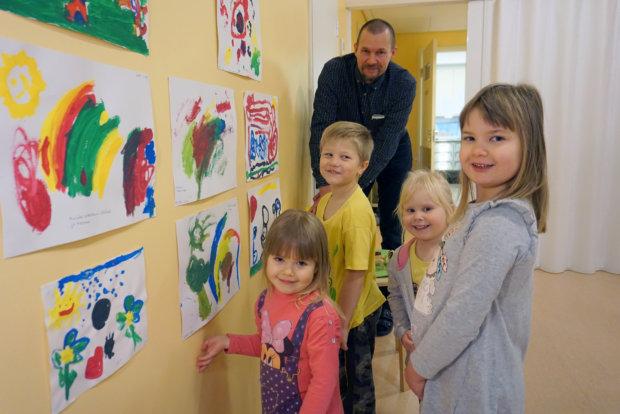 Hermannin päiväkodin lapset Lempi Nuuttila (edessä vasemmalla), Henni Penttinen, Nella Vuorijärvi ja Reino Haulivuori esittelevät Jari Markkiselle eläinaiheista taidenäyttelyä.
