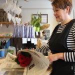 Eija Laakson käsissä kukkapaketti syntyy nopeasti, kun paperit ovat oikean kokoisia.