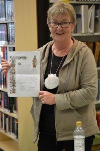 Paula Nurmi kädessään pyhiinvaeltajan diplomi.