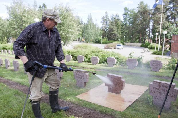 Hannu Liesilä pesi sankarihautausmaan kiviä kuumapainepesurilla. Nurmen suojaksi reserviläiset ovat nikkaroineet puulevyt.