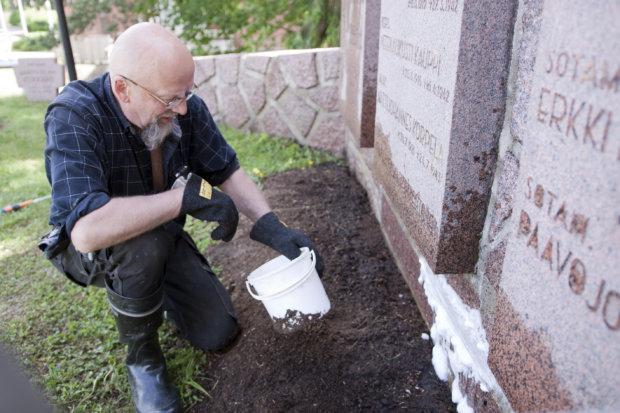 Kalevi Koivisto puhdisti sankarimuistomerkin hapolla vaaleista kalkkihuuhtoumista.