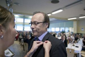 Pentti Lahtinen saa Sanna Laineelta kultaisen ansiomerkin.