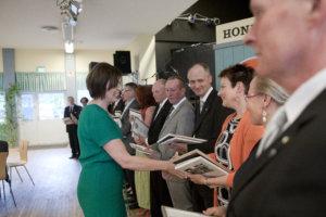 Satavuotisjuhlassa palkittiin pitkä rivi pankin puolesta toimineita. Toimitusjohtaja Sirpa Leppäkoski onnittelee hopeisella ansiomerkillä palkittua Jaana Jokista.