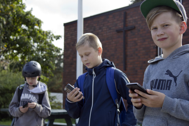 Eeli Nikkanen, Rasmus Johansson ja Severi Penttinen jahtaavat koulupäivän päätteeksi Pokemoneja seurakuntatalon luona.