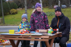 Miko, Noora ja Marko Koskinen oman myyntipöytänsä takana.