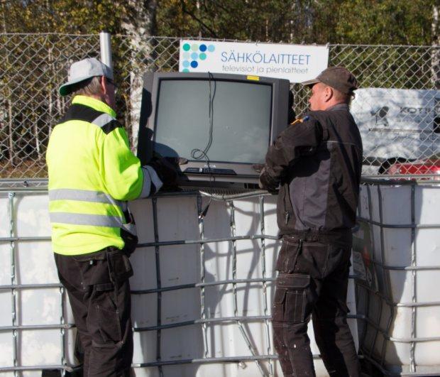 Pekka Ilmoni ja Jari Volanen Harjulan pajalta kantavat rikki mennyttä televisiota sähkölaitteille varattuun paikkaan.