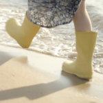 Pienet keltaiset kumisaappaat tulevilla rannoilla