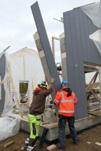 Markku Juutilainen ja Kari Alho nostavat ensimmäisen minitalon seinäelementtejä paikalleen.
