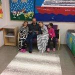 Kodin ja koulun päivä. Lukuhetkessä Juha Kankariston kanssa Rebekka ja Sara Kankaristo sekä Julianna Marko.