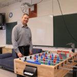 Pälkäneen lukion rehtori Jan Salmi esittelee uutta pöytäjalkapallopeliä.