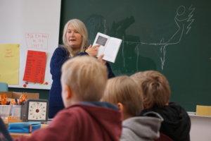 Tiina Poutanen kertoi oppilaille erilaisten merkkien, kuten kalliomaalausten, hieroglyfien, meemien ja hymiöiden, kielestä.