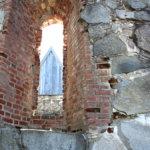 Rauniokirkon tiilet ovat lohkeilleet ja kiviä on pudonnut seinistä.