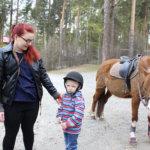 3-vuotias Oliver Saarela keräsi rohkeutta. Taustalla tarkkailee Sebastian-hevonen juhlahatussaan.