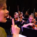 Aira Maria Lehtipuu harjoituttamassa Seljanikoita. Taustalla islantilaisorkesterin johtaja Unnur Pálsdóttir.