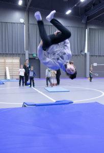 Yläkoululaispojat ovat harjoitelleet näyttäviä voltteja trampoliinilla. Tässä vauhdissa Toivo Saarinen.