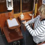 Kostian veneseuran kommodori Maaria Helin-Tervo on Bertan puosu. Hän puuhaa siis kaikkea, mitä veneessä täytyy puuhata. Tässä hän selvittää köysiä veneen taka-avotilassa.
